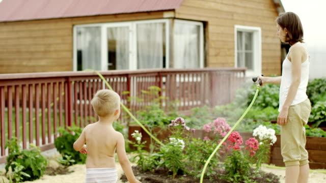 gartenbewässerung mit einem schlauch - urban gardening stock-videos und b-roll-filmmaterial
