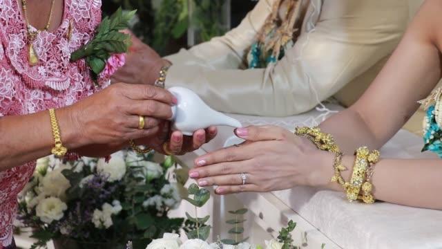 vídeos de stock e filmes b-roll de watering the conch shell in wedding thailand style. - bugio