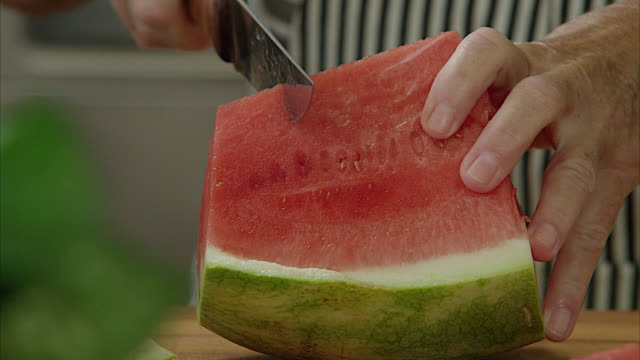 Watermelon on kitchen counter Cutting and Slicing a watermelon on a butcher block counter. watermelon stock videos & royalty-free footage