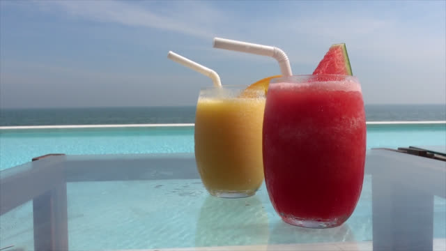 watermelon smoothie and mango smoothie with swimming pool and sea background - vídeo