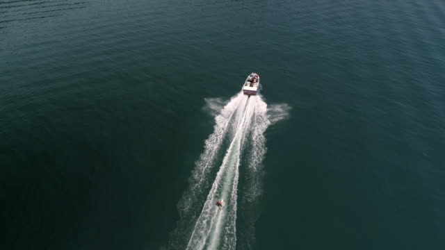 Waterski Aerial of Drone Flying Over Boat Pulling Man on Beautiful Blue Water video