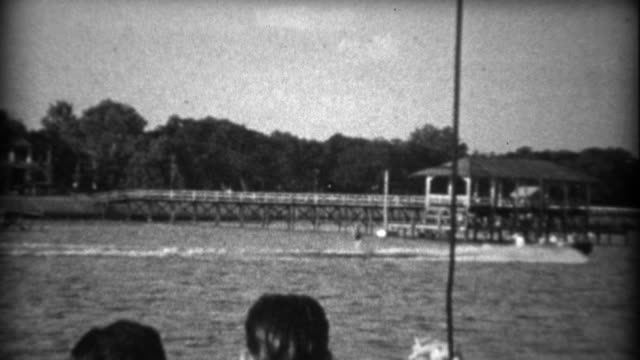 1934: Waterskiing across gulf coast mansion sailboats and pier backdrops. video