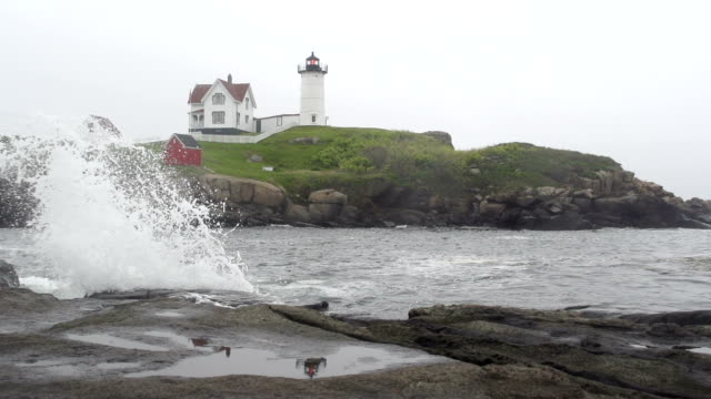 Wave Breaking Over Rocky Shoreline with Lighthouse in Distance