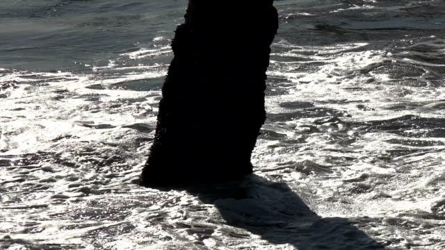 A wave crashing into a pier