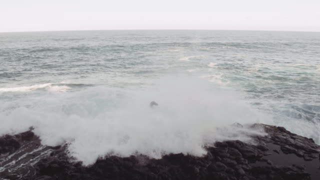 Wave crashing over man Wave crashing over man while his arms are raised in victory cliff jumping stock videos & royalty-free footage