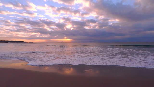 welle am strand am morgen und sonnenaufgang bis 4 k - horizont über wasser stock-videos und b-roll-filmmaterial