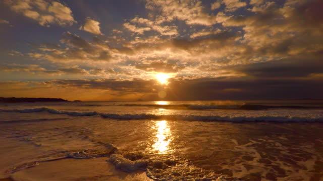 vídeos de stock e filmes b-roll de onda na praia ao nascer do sol de manhã e 4 k - linha do horizonte sobre água