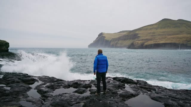 Wave passed on man in blue raincoat