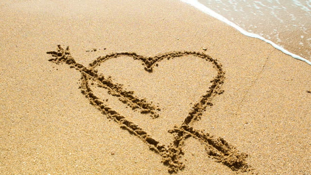 Wave washes over heart in the sand. Love and heart break concept. video