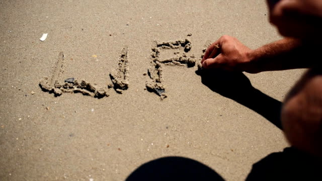 Wave washes the word life written on sand