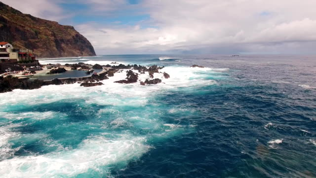 Waves and rocks near city and pools of Porto Moniz aerial view