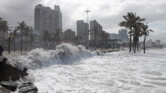 Waves breaching barrier wall at Durban's beachfront. Turbulent sea breaches barrier wall protecting Durban's beach promenade caused by strong winds after a storm on the 18 October 2014. coastal feature stock videos & royalty-free footage