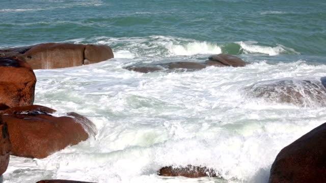 Waves Breaking on Coastal Pink Stone Boulders. video