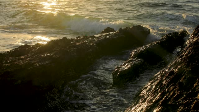 Waves Breaking On Rocky Coastline With Sun Glistening On The Waves
