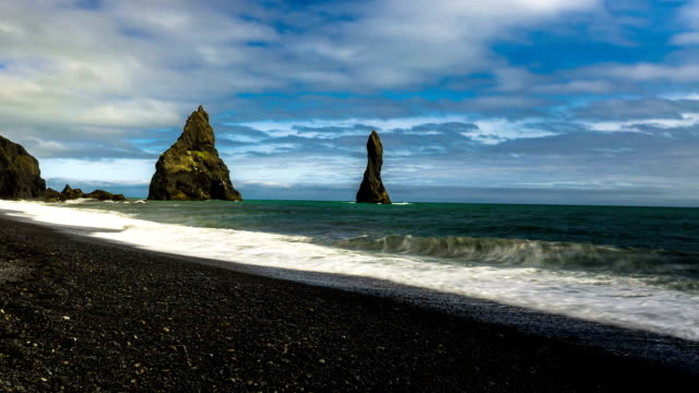 Waves breaking on the black sand beach. Basalt columns, towering 70 meters above the waters of the North Atlantic. Reynisdrangar beach, Iceland video