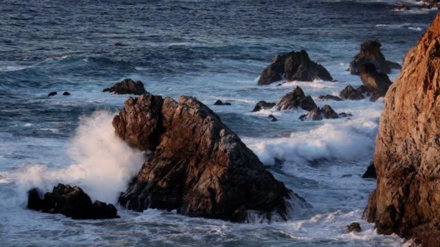 vídeos de stock e filmes b-roll de ondas estoiro rugosa big sur ao longo da costa da califórnia-do-sol - montanha costeira
