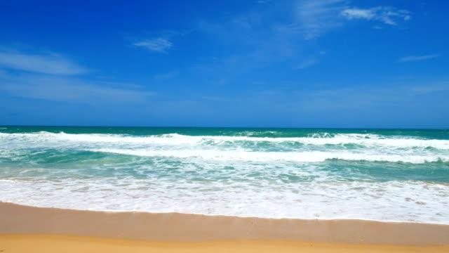 vídeos de stock e filmes b-roll de waves crash on a tranquil deserted beach in naiharn beach. at phuket, thailand. on july 30, 2018 - plano picado