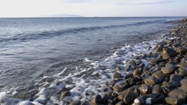 Waves crash on rocky shore, slow motion