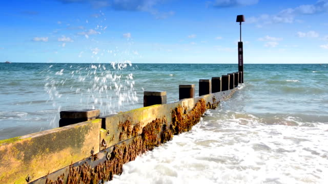 Waves crash on woodne beach groyne video