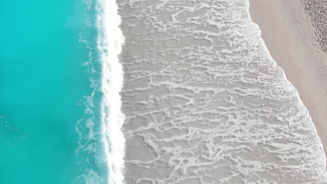 Waves crashing  at the sandy beach, shot from drone Waves rolling back into the ocean leaving wet sand. Colorful travel concept, nature beauty greek islands stock videos & royalty-free footage