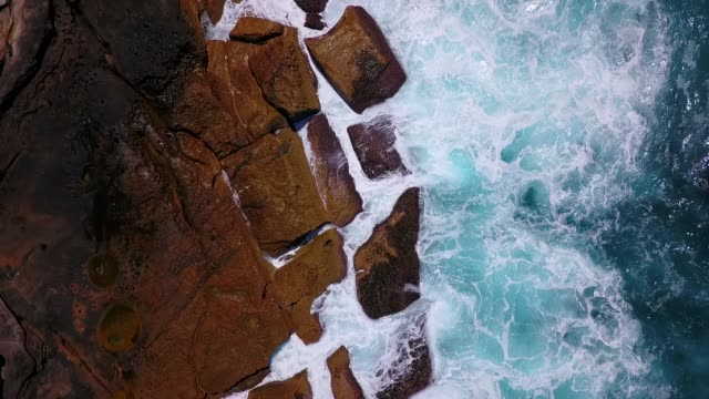 Waves crashing into a rocky coastline Aerial view of dramatic waves crashing against a rocky shoreline in Australia. 天の川 stock videos & royalty-free footage