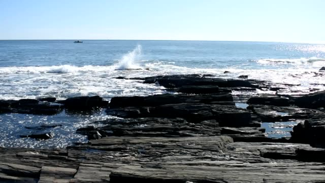 waves crashing into a rocky shoreline - mit audio - sound wave stock-videos und b-roll-filmmaterial