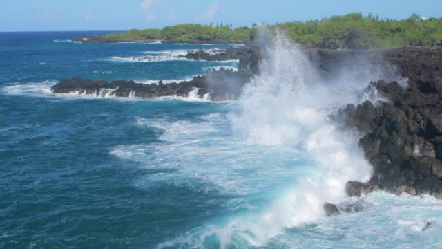 Waves crashing into shore on Hawaii Beautiful blue ocean and large waves crashing into shore on Hawaii. big island hawaii islands stock videos & royalty-free footage