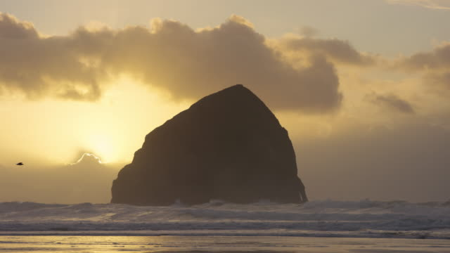 Waves crashing on rocks at the beach at sunset