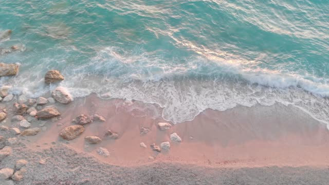 Waves crashing on rocks at the sandy beach at sunset, shot from drone