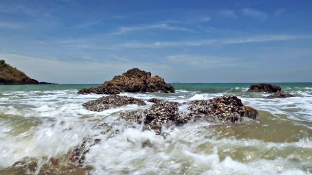 Waves crashing over rocks on beach seascape, Bamboo Bay, Ko Lanta, Thailand