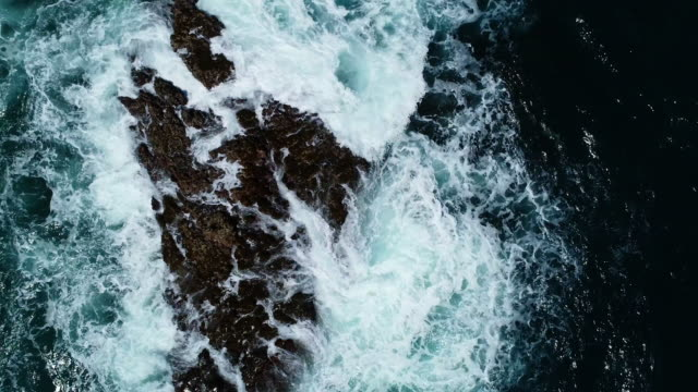 waves on a rocky beach - pietra roccia video stock e b–roll