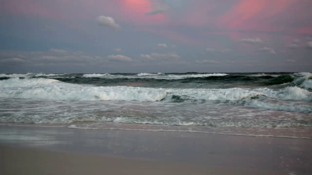 Waves on beach colored sky.