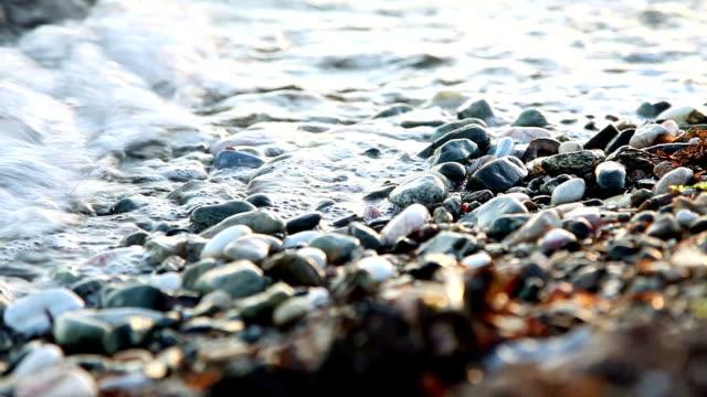 waves on rounded pebbles - kontrastrik bildbanksvideor och videomaterial från bakom kulisserna
