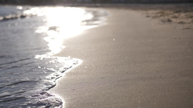 waves on the beach at sunset in Spain, waves with foam slow motion video