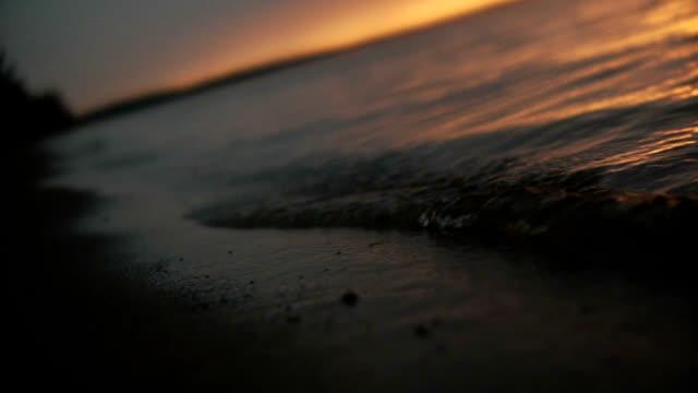 vídeos de stock e filmes b-roll de ondas na praia ao pôr do sol de luz - margem do lago