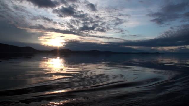 Golven op het wateroppervlak op de achtergrond van donkere hemel en grijze wolken bij zonsondergang. video