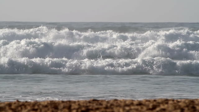 Waves rolling towards the sand beach on a sunny day video