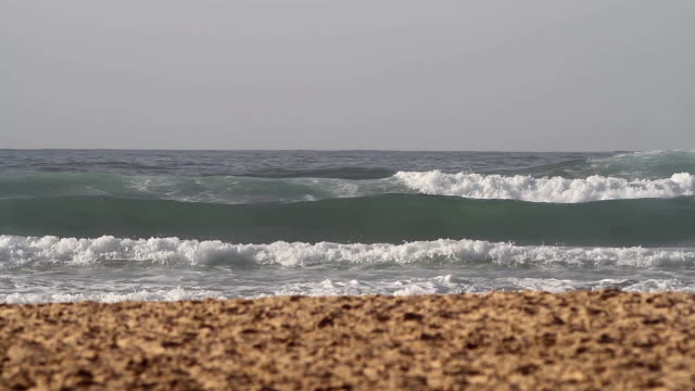 Waves rolling towards the sand beach video