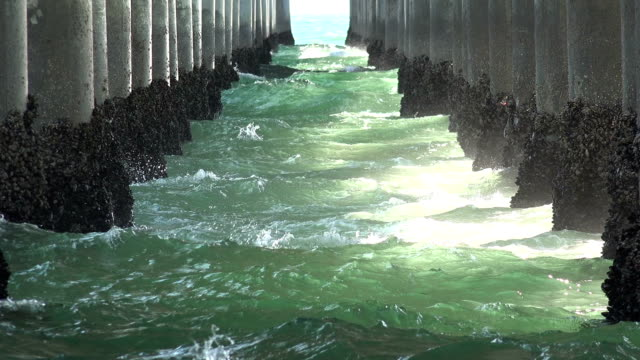 Waves rushing in under a pier
