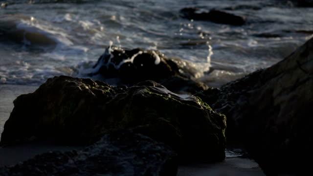Waves Slowly Crashing Over Rocks on Beach video