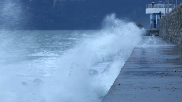 Waves splashing and gale force wind gusts harbor pier
