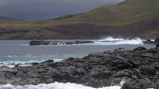 SLOW MOTION: Waves splashing over the black rocks on their way to the coastline. video