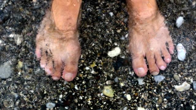 Waves splashing water on man's feet by the sea video