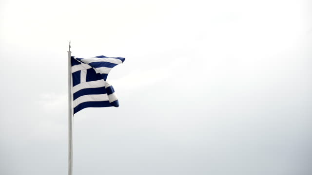 waving a greece flag on a cloudy sky. - grecia stato video stock e b–roll