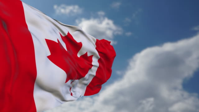 Waving Canadian flag in sky.