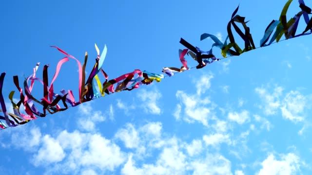 vifta färgade band på ett rep i en blå himmel med moln. - blue yellow band bildbanksvideor och videomaterial från bakom kulisserna