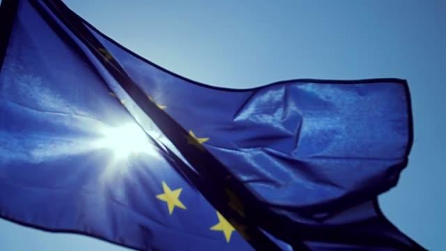 winken eu-flagge im wind mit einem blauen himmel. - europäische union stock-videos und b-roll-filmmaterial
