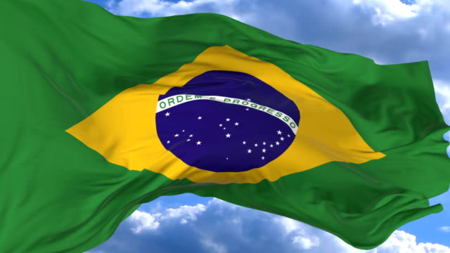 vídeos de stock, filmes e b-roll de agitando a bandeira contra o céu azul brasil - insígnia