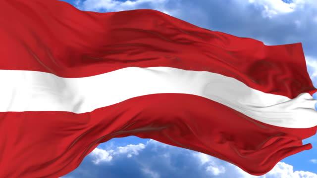 waving flag gainst the blue sky latvia - insygnia filmów i materiałów b-roll