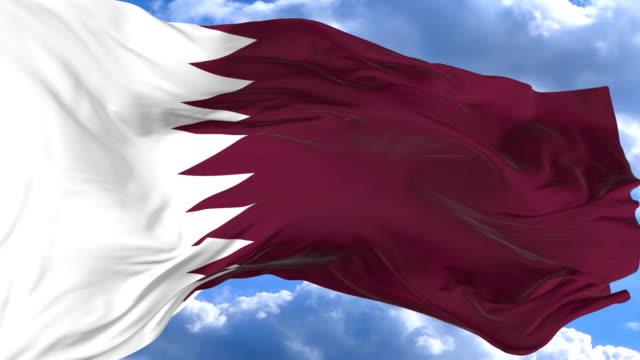 waving flag gainst the blue sky qatar - insygnia filmów i materiałów b-roll